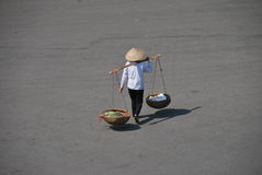 Vietnamese girl crossing the street. In Hanoi Vietnam on her way to the market with her goods Royalty Free Stock Photos
