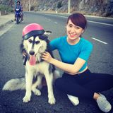 Vietnamese girl with dog in pink hat. Sitting on road in Vietnam Royalty Free Stock Images