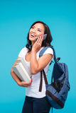 Vietnamese girl holding backpack and books talking on the phone Royalty Free Stock Photography