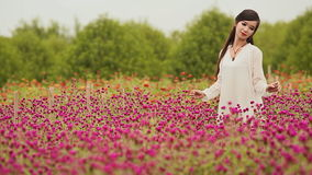 Vietnamese girl with long black hair standing in a plantation purple flowers. stock video
