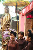 Vietnamese Girls in Ao Dai stand in front of Guanyin statue Stock Images