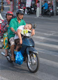 Vietnamese grandparents and grandson on motorbike. HO CHI MINH CITY - MARCH 28, 2015: Unidentified senior man and woman drive by motorcycle with their sleeping Royalty Free Stock Photography