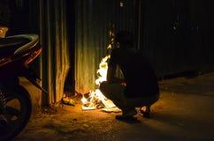 Vietnamese guy burning paper at night stock photo