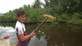 Vietnamese Guy Does Fishing with Rod from Bank of Small River stock video