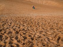 Hawker. Vietnamese Hawker Walking in Red Sand Dunes, Poppular Travel in Mui Ne, Vietnam on Sunny Day royalty free stock images