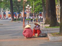 Vietnamese Hawkers. 2 Vietnamese hawkers chatting while waiting for customers. Ideal for writeup on Vietnamese lifestyle Stock Photo