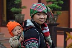 Vietnamese Hmong-Frau, die ihr Kind trägt Stockbild