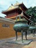 Vietnamese Imperial Palace. Large weathered green bronze urns in front of a Vietnamese style building (Hien Lam Cac Pavilion) in the Imperial Palace, Hue Stock Photo
