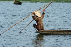Vietnamese Man In A Boat. Man in a fishingboat on a river in Vietnam Stock Image