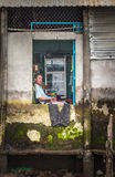 Vietnamese man looking through a window, Mekong Delta Stock Photography