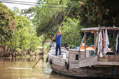 Vietnamese man rowing his houseboat Royalty Free Stock Images