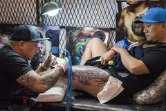 Vietnamese man wearing a cap is getting a tattoo on his left leg by DCN, Tattoo Tu Nguyen stock photography