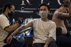 Vietnamese man wearing a white t-shirt is getting a tattoo on his right arm by Recycle Tattoo Studio. stock photos