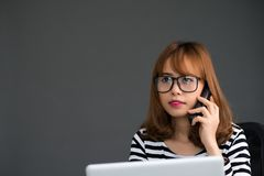 Vietnamese manager. Female manager talking on phone in office Stock Images
