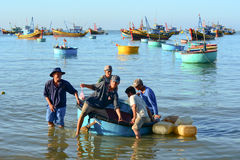 Vietnamese men with the basket boat in Mui Ne town, Vietnam Royalty Free Stock Image