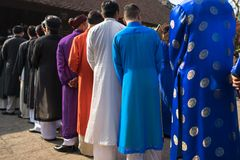 Vietnamese men wear traditional long dress Ao Dai standing at ancient village communal house.  Stock Photos