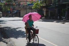 Vietnamese mens met roze paraplu berijdende fiets Royalty-vrije Stock Afbeeldingen