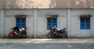 Vietnamese motorbike taxi driver sleeping on motorcycle Royalty Free Stock Photography