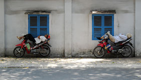 Vietnamese motorbike taxi driver sleeping on motorcycle Royalty Free Stock Images