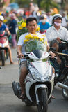 Vietnamese motorcyclist with yellow flowers for Tet (Lunar New Y Royalty Free Stock Photography