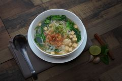 Vietnamese noodle pork sausage soup ( pho) in white bowl. On wooden background royalty free stock photo