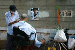 Vietnamese open air barber shop on pavement Stock Photography