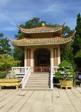 The Vietnamese pagoda is surrounded by beautiful trees and shrub. S. Against the blue summer sky Royalty Free Stock Photography