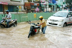 Vietnamese people, flooded water street. HO CHI MINH CITY, VIET NAM- OCT2: Group of Vietnamese people ride motorbike, bike moving on flooded street after rain Stock Image