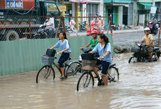 Vietnamese people, flooded water street. HO CHI MINH CITY, VIET NAM- OCT2: Group of Vietnamese people ride motorbike, bike moving on flooded street after rain Royalty Free Stock Photos