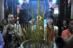 Vietnamese people offering incense sticks for the Gods. SAIGON - FEB 18: Unidentified believers praying and offering incense sticks for the Gods in the Royalty Free Stock Images