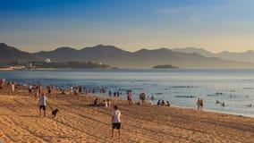 Vietnamese people walk on beach swim in sea at dawn. NHA TRANG, KHANH HOA/VIETNAM - AUGUST 19 2015: Vietnamese people walk on sand beach and swim in tranquil sea stock video footage
