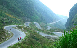 Vietnamese people walking on a long mountain road. To the light of sunrise Stock Photos