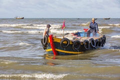 Vietnamese people working on boat. At Long Hai beach, Ba Ria Vung Tau province, Vietnam. This is an air fish market on the beach. The nearest woman in conical Stock Image