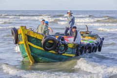 Vietnamese people working on boat. At Long Hai beach, Ba Ria Vung Tau province, Vietnam. This is an air fish market on the beach. The nearest woman in conical Stock Images