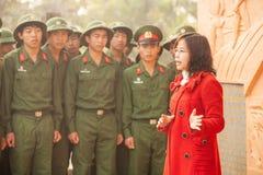 Vietnamese professorsvrouw die aan jonge Vietnamese militair bij standbeeld van Franse General DE Castries spreken stock afbeelding