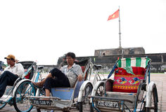Vietnamese rickshaw driver. HUE, VIETNAM - SEPTEMBER 2, INDEPENDENCE DAY: Vietnamese rickshaw driver waiting for customers in front of the Flag Tower overlooking Stock Images