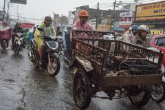Vietnamese riders keep on going under the rain on a street of Ho Chi Minh City, Vietnam stock photo