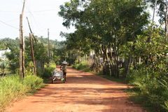 Vietnamese road. This picture was taken on the island of Phu Quoc in Vietnam. I love the dirtroad in combination with the traditional rice hat the person on the Royalty Free Stock Images
