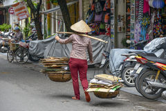 Vietnamese sales woman in Hanoi. It's very common to see the street vendors carrying their goods along on the street in Hanoi, North Vietnam Stock Image