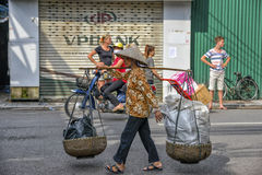 Vietnamese sales woman in Hanoi. It's very common to see the street vendors carrying their goods along on the street in Hanoi, North Vietnam Royalty Free Stock Photos