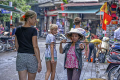 Vietnamese sales woman in Hanoi. A street vendor with her goods in the streets of the old quarter in Hanoi, Vietnam, is showing tourists the way Royalty Free Stock Images