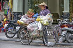 Vietnamese sales woman in Hanoi. A street vendor is selling her fruit in the streets of the old quarter in Hanoi, Vietnam Royalty Free Stock Photo