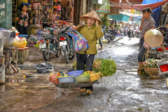 Vietnamese sales woman in Hanoi. A street vendor is walking with her goods on the street in the old quarter of Hanoi, North Vietnam Royalty Free Stock Photo