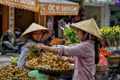 Vietnamese sales women in Hanoi. Street vendors on the street in the old quarter of Hanoi, North Vietnam Royalty Free Stock Image
