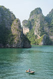 Vietnamese saleswoman from boat on the water. Halong bay Royalty Free Stock Images