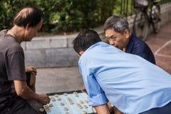 Vietnamese seniors playing board game. Vietnamese playing board game outside stock image