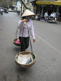 Vietnamese shop assistant assistant going along streets looking for the buyer Stock Photography