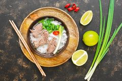 Vietnamese soup pho dish. Asian cuisine. Vietnamese soup on a dark rustic background. View from above. The concept of Asian cuisin