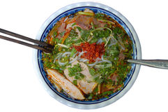 Vietnamese Spicy Beef Noodle (Bun Bo Hue). A bowl of Vietnamese spicy beef noodle (bun bo Hue), top view, isolated on white Royalty Free Stock Photos