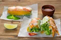 Vietnamese spring rolls with shrimps and sauce on wooden background stock photo